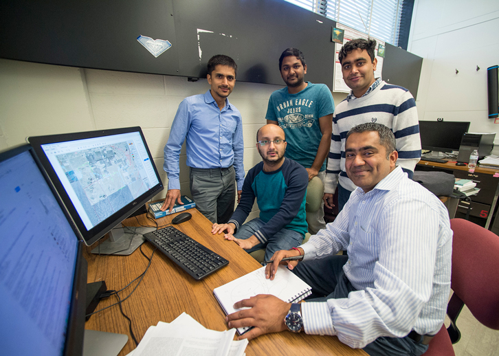 Researchers pose around a computer