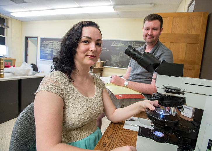 Student researcher and professor at microscope