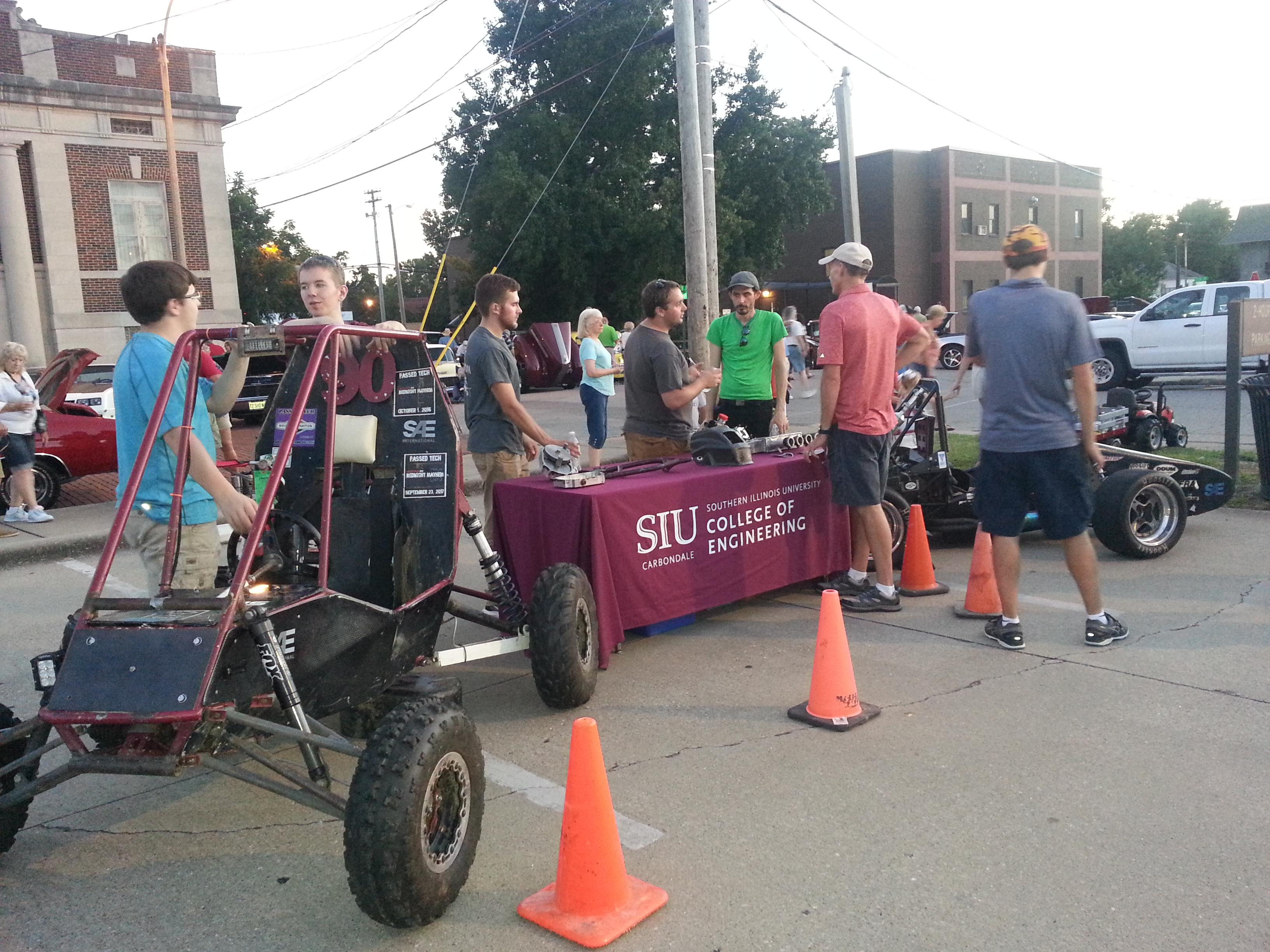 Students at table next to baja car