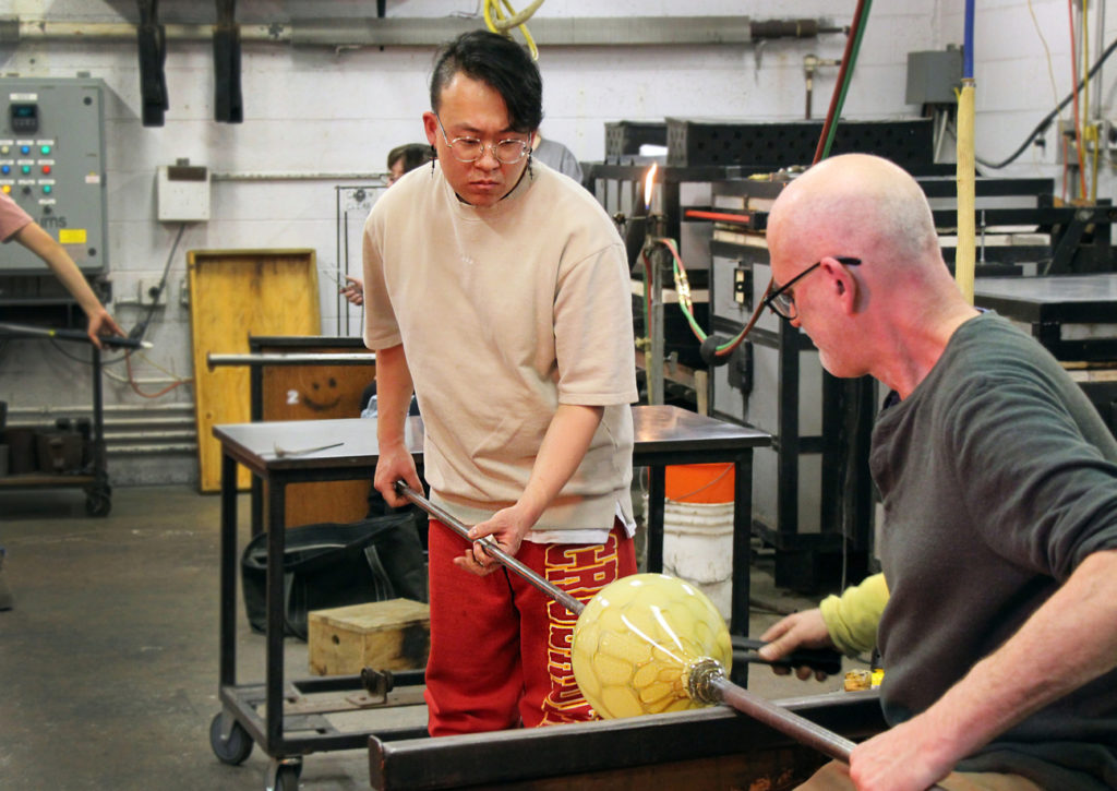 Ho Seok Youn using pipes and tweezers to shape glass vase.