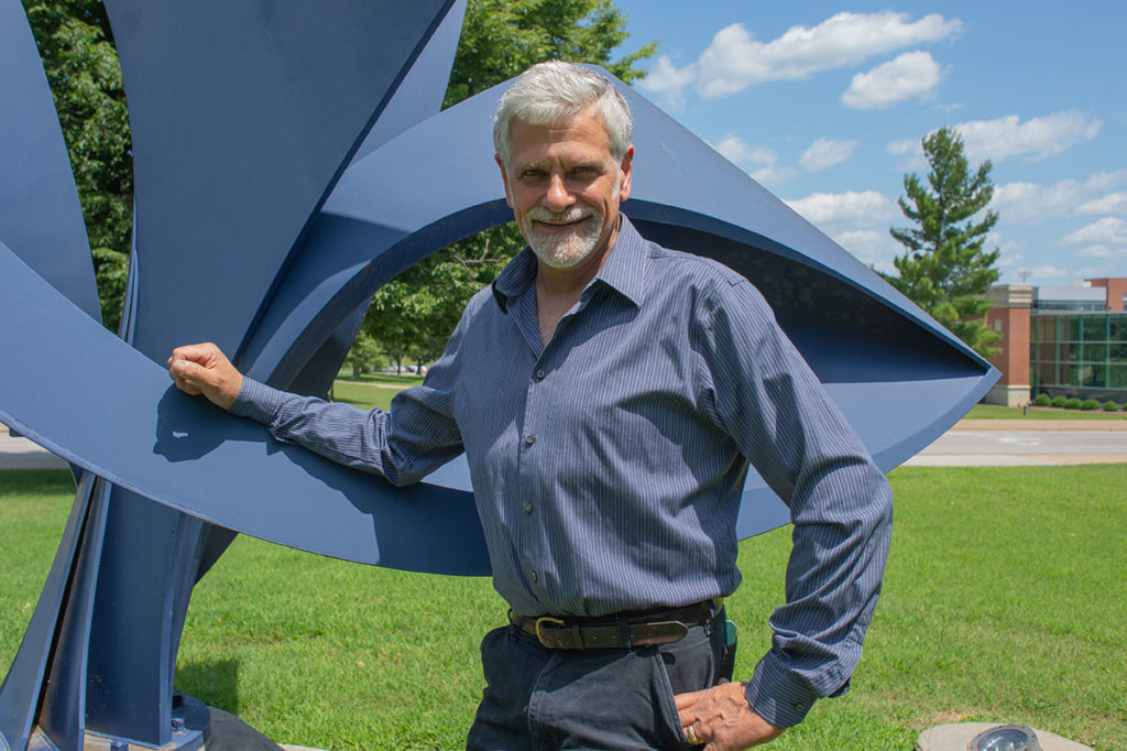 John Medwedeff next to his metal sculpture