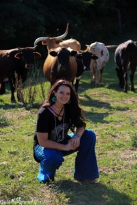 Kaitlin in a field with cattle.