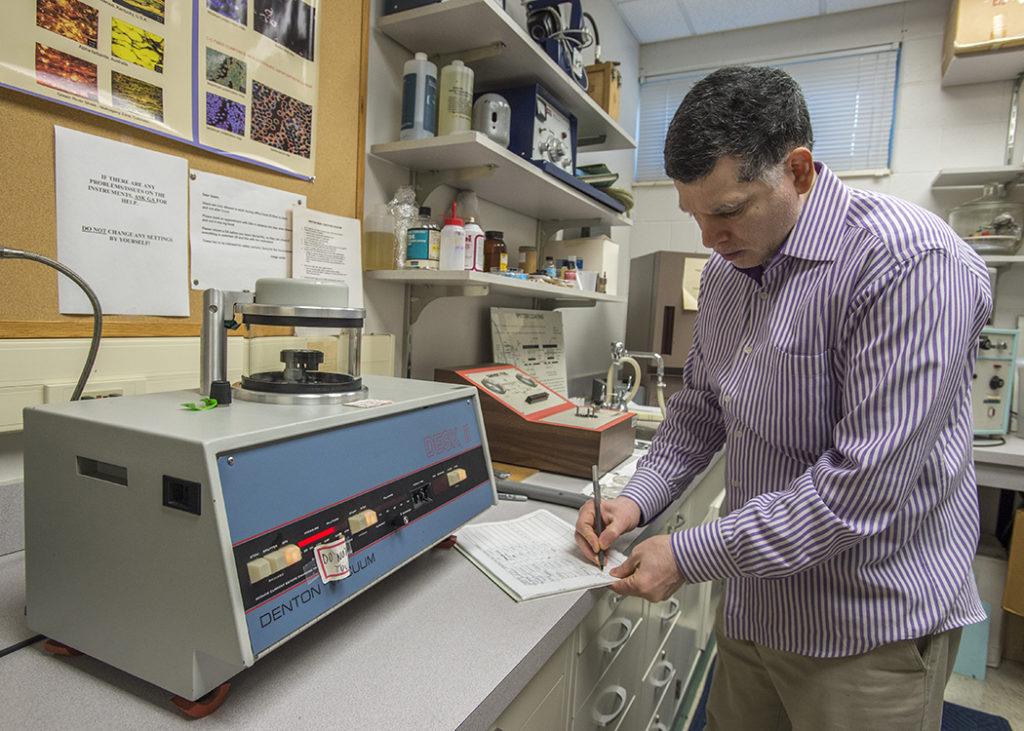 Punit Kohli takes notes near plasma coating machine.