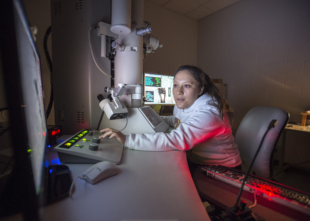 Student works on transmission electron microscope.