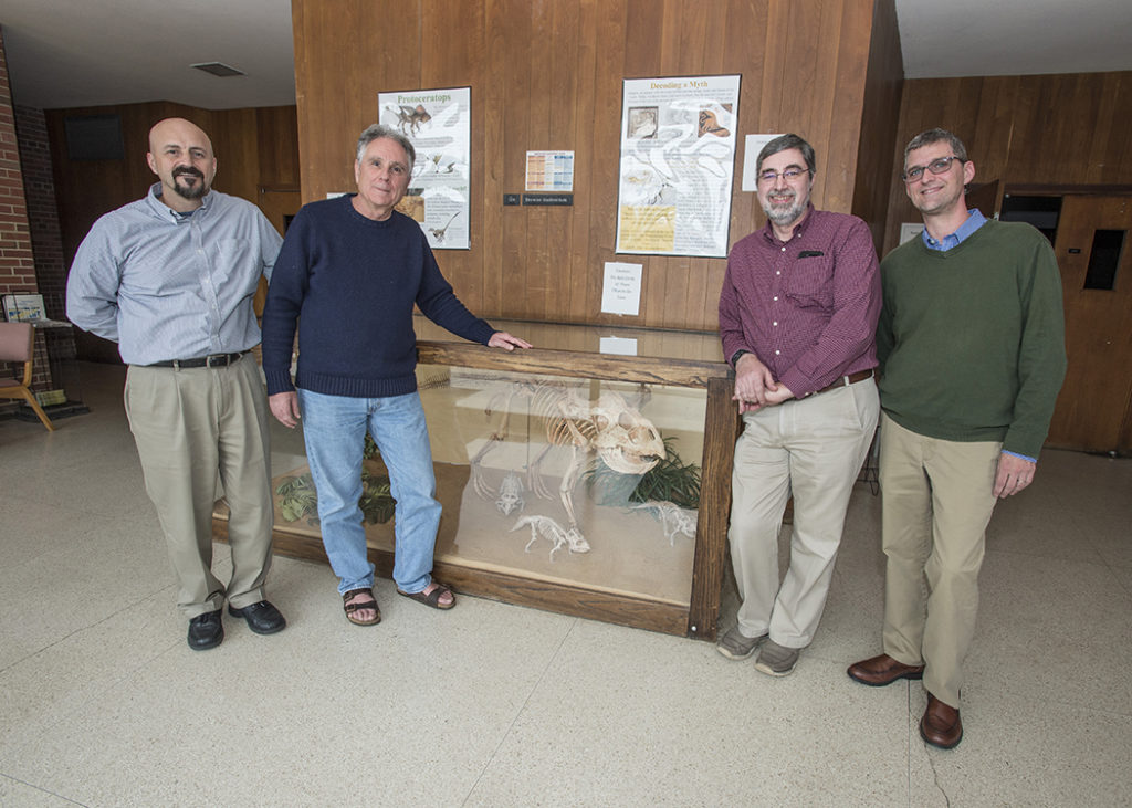 SIU faculty with dinosaur display.