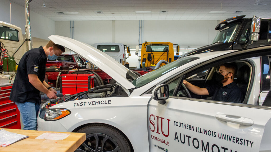 Students Justin Gill (under the hood) and Kyle Serna (in car) are preparing for insulation testing between the 2018 Ford Fusion hybrid's disabled high-voltage system and chassis.