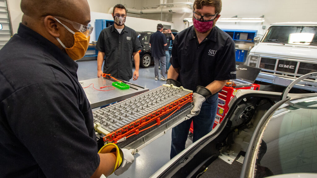 Students Marquise Phipps, left, and Kyle Keck, right, are removing a battery-pack from a 2012 Toyota Camry hybrid for student Brendan Ramsey, center, to diagnose.