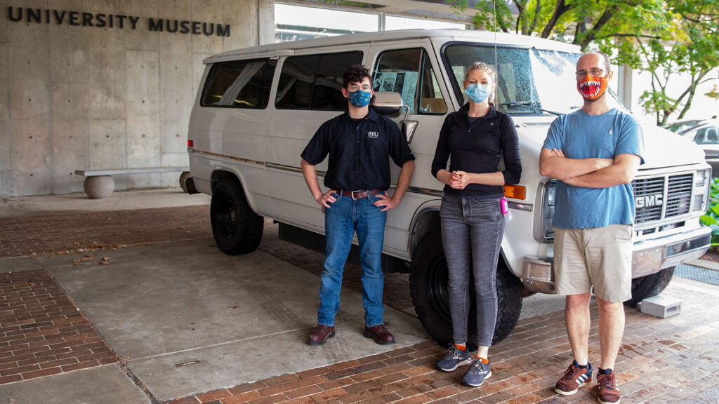 arker Rippinger, left, a student in the electric vehicle propulsion course, Jessica Suda, center, an assistant professor in the automotive technology program, and Wes Stoerger, right, University Museum curator, are with the 1991 GM electric GVan that will be part of an upcoming exhibition at University Museum.